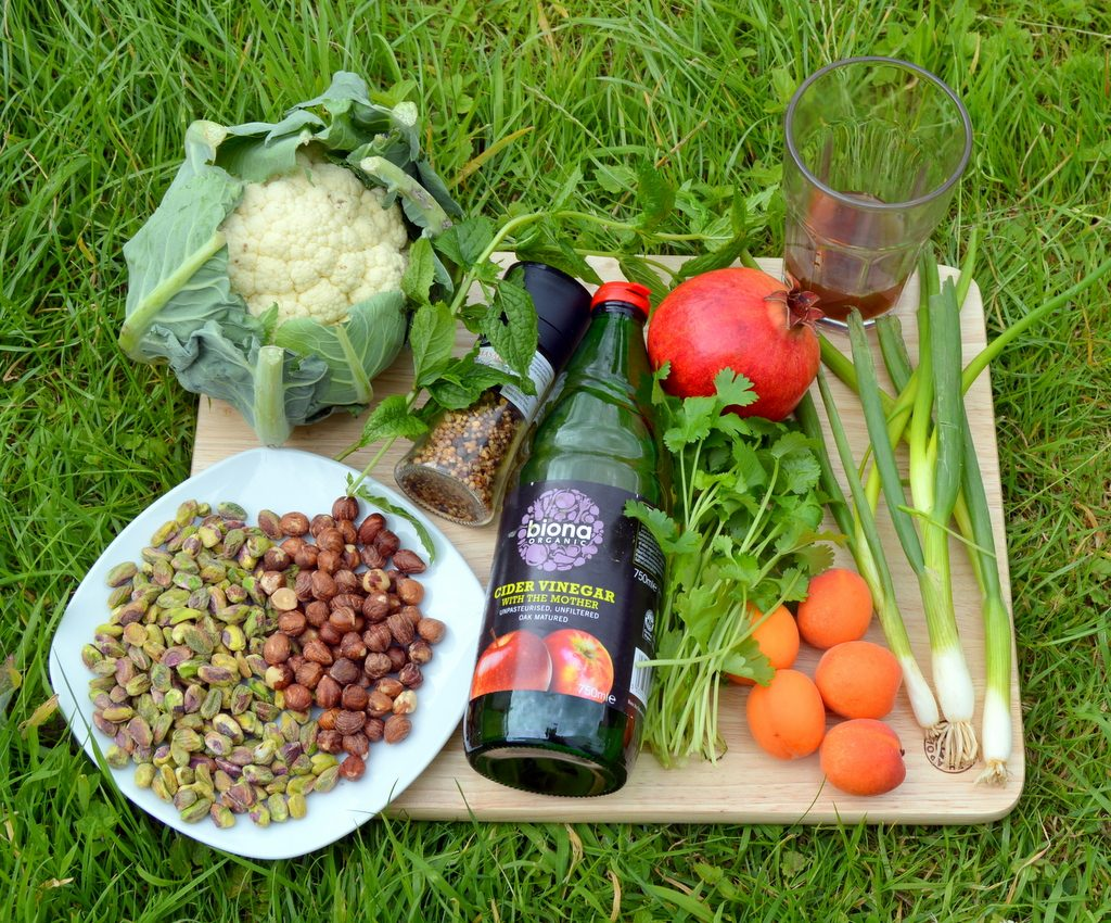 ingredients for Fruity nutty cauliflower couscous crunch including apricots, pistachios, hazelnuts, apple cider vinegar and spring onions.
