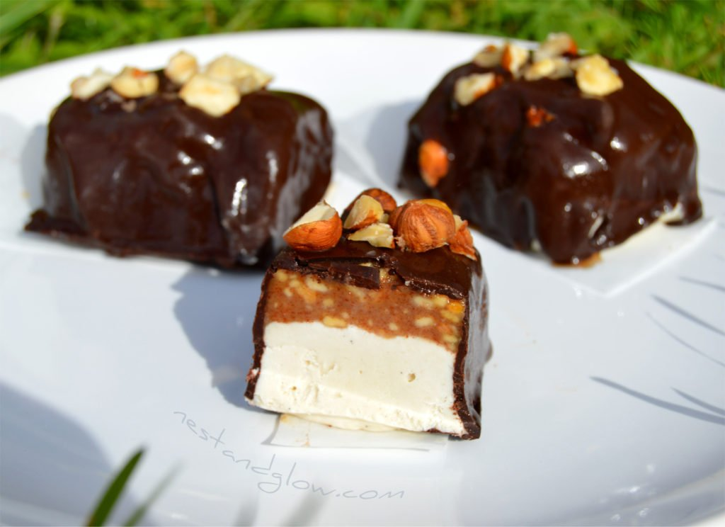 snickers raw vegan ice cream on a plate and cut with a knife to show the crunchy almond butter caramel. Everyone loves these dairy free amazing ice cream bars