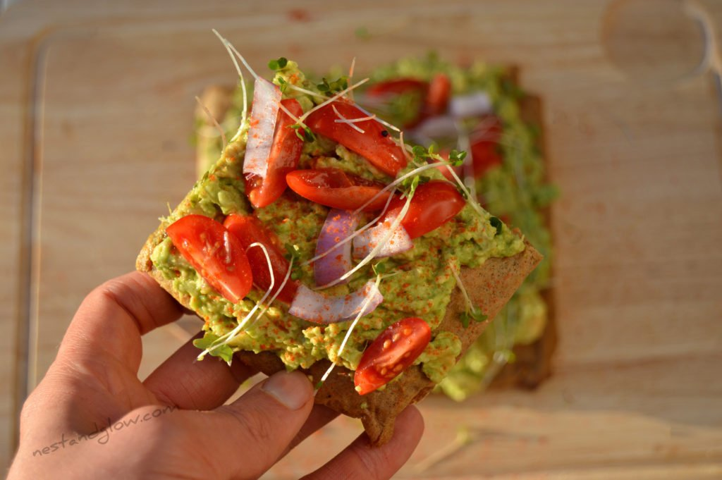 A slice of avocado toast on made from gluten free quinoa bread