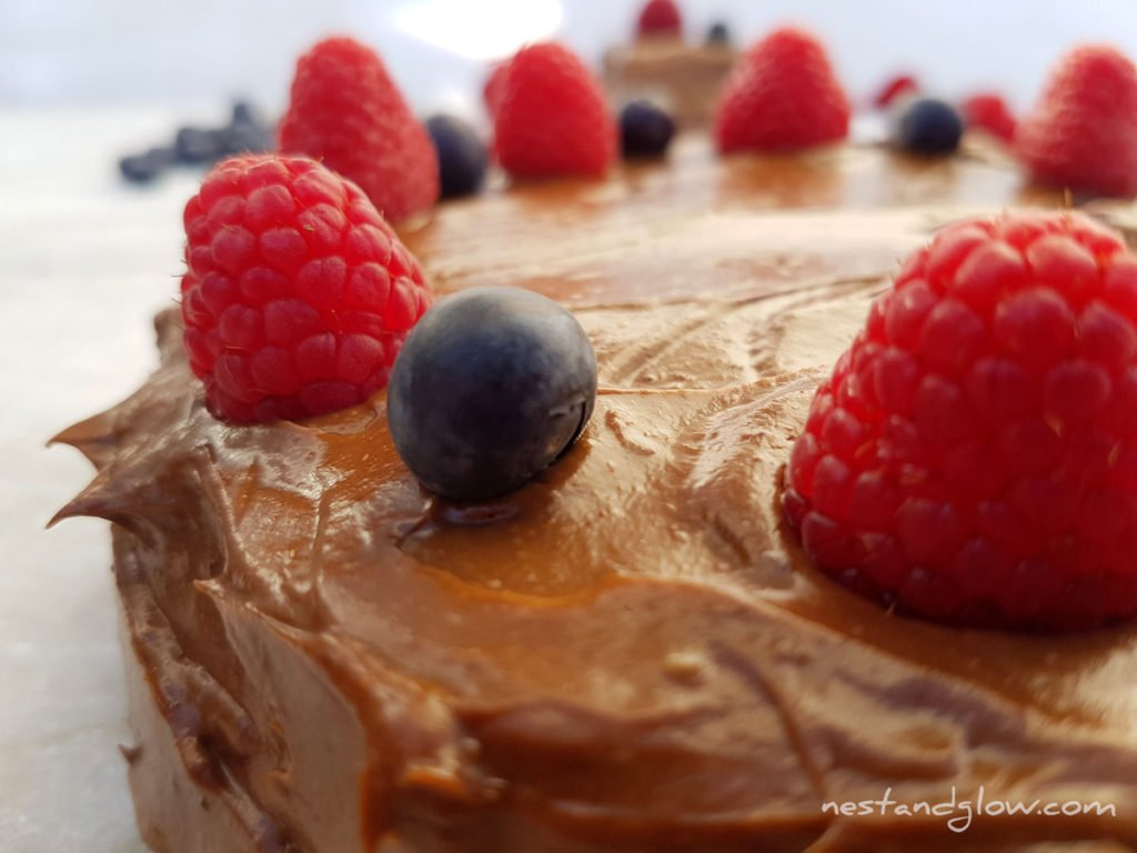 Quinoa Chocolate Cake With avocado frosting, raspberries and blueberries close up
