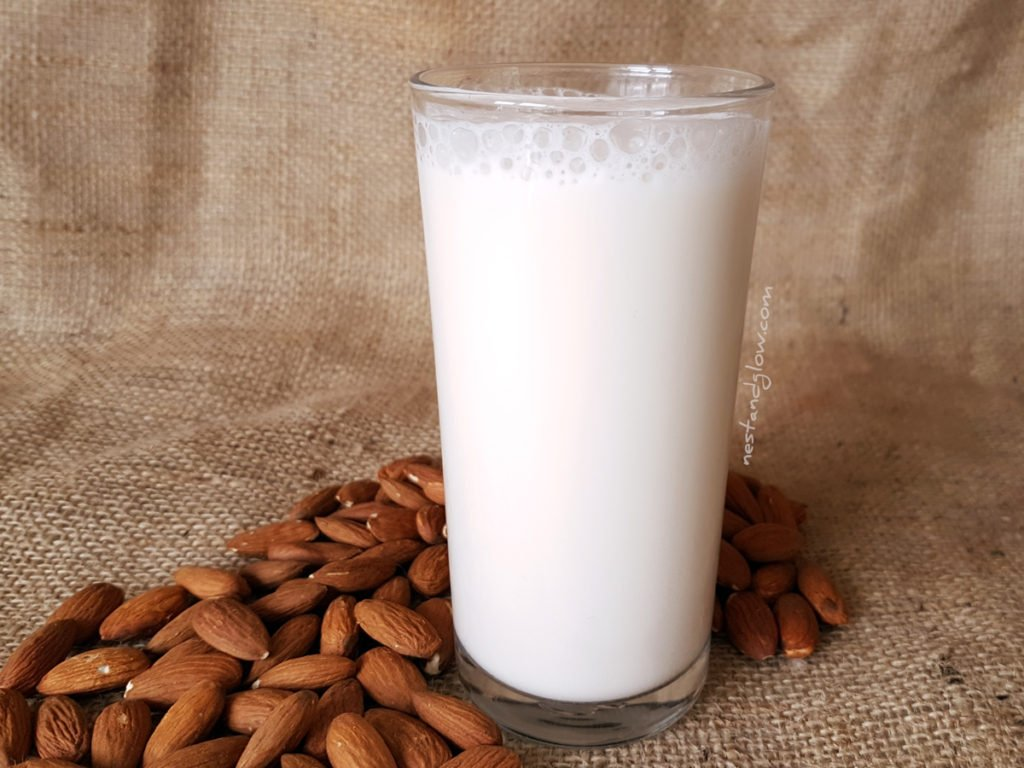 A glass of easy almond milk that's had a touch of natural sweetness and vanilla added. This simple almond milk is so versatile to use and a great way to save money