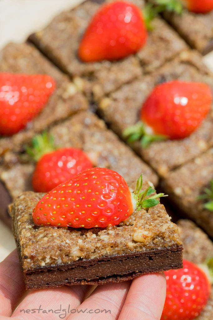 strawberries on top of a high protein vegan brownie. no oil, no butter and no junk in this healthy chocolate brownie