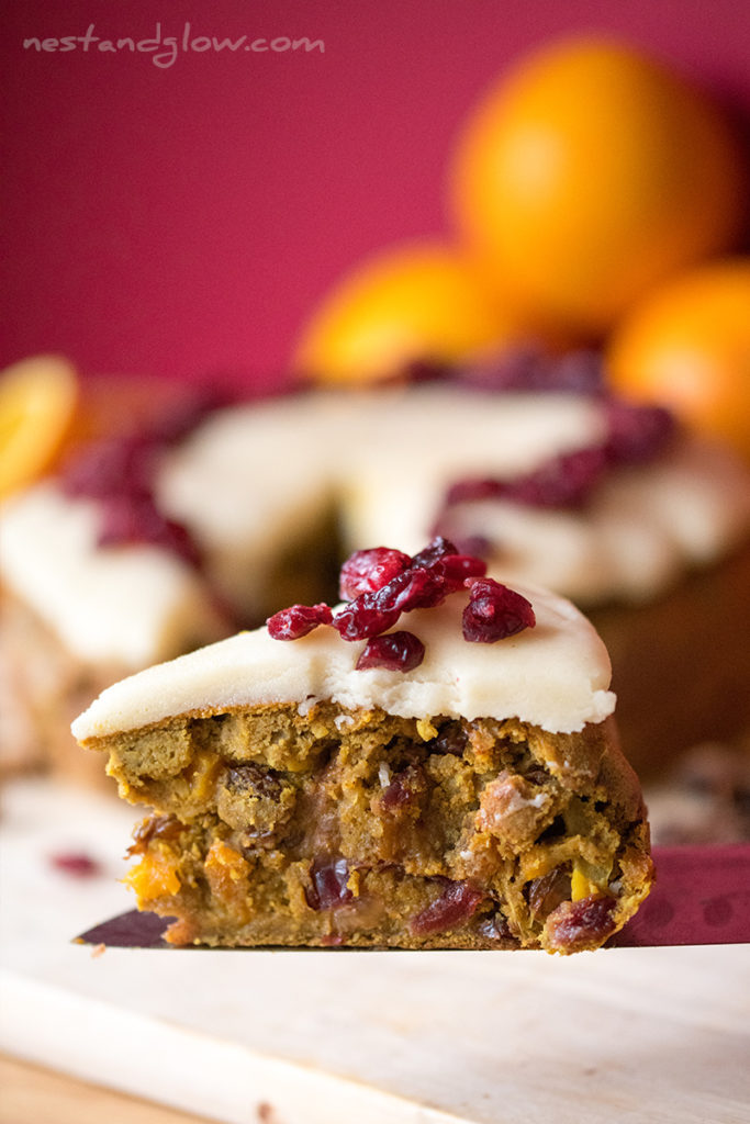 quinoa fruit cake slice on a knife and topped with marzipan and cranberries.